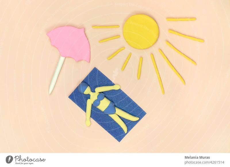 Women laying on the beach under pink umbrella taking a sunbath in bikini on the towel. Top view, artificial scene. Concept of summer holiday. above view