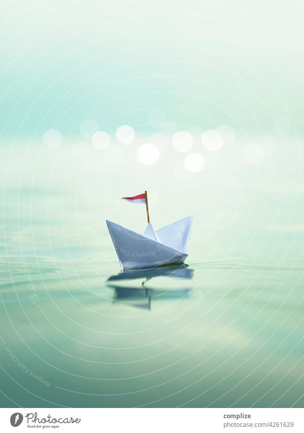 Paper ship on the sea voyage travel Vacation mood Swell glossy Glimmer Sunset vacation bokeh paper boat Passenger ship Summer Sailing Waves Beach