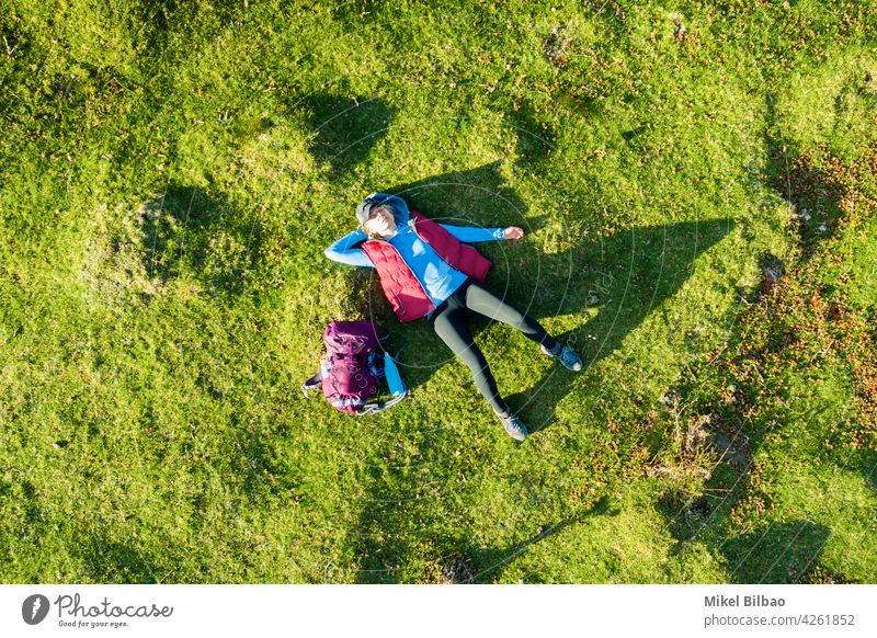 Aerial view of a young woman hiker with a backpack lying on his back on a meadow. lifestyles aerial vacations excursion Spain travels tourism wanderlust people
