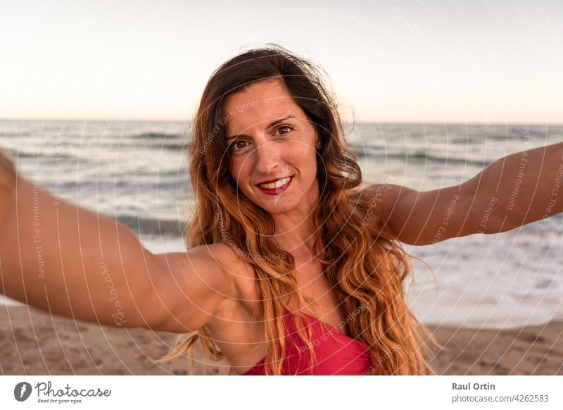 Pretty stylish woman having fun taking a selfie on beach at sunset. sea summer happy camera nature outdoor lifestyle use smartphone young adult cell phone
