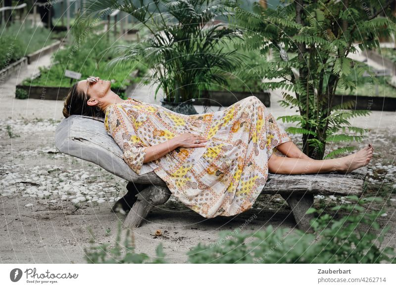 Woman in dress lying relaxed on a wooden lounger in a garden pretty Lie Couch Garden Dress vacation chill Summer voyage Vegetable bed plants Green Nature