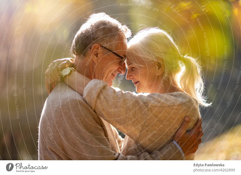 Elderly couple embracing in autumn park family woman love people outdoors portrait together nature two beautiful fall trees yellow senior mature seniors