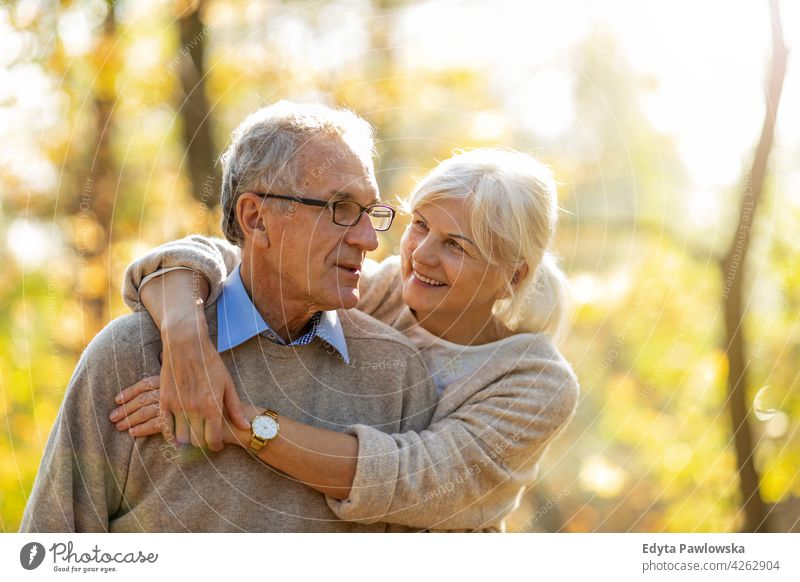 Senior couple in autumn park family woman love people outdoors portrait together nature two beautiful fall trees yellow senior mature seniors pensioner