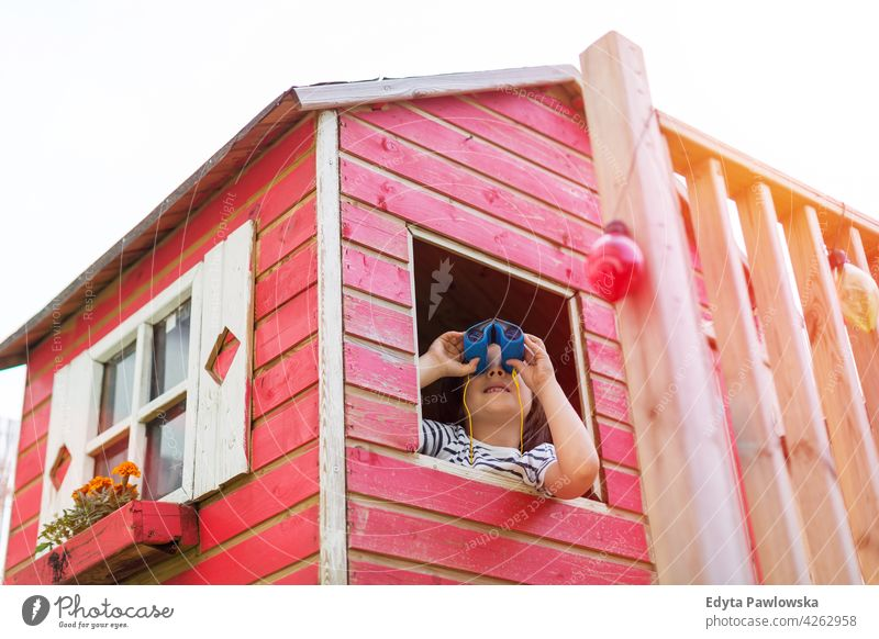Boy in a wooden playhouse looking through a binocular binoculars holding adventure exploration red Sweden tree tree house treehouse summer outdoors playful