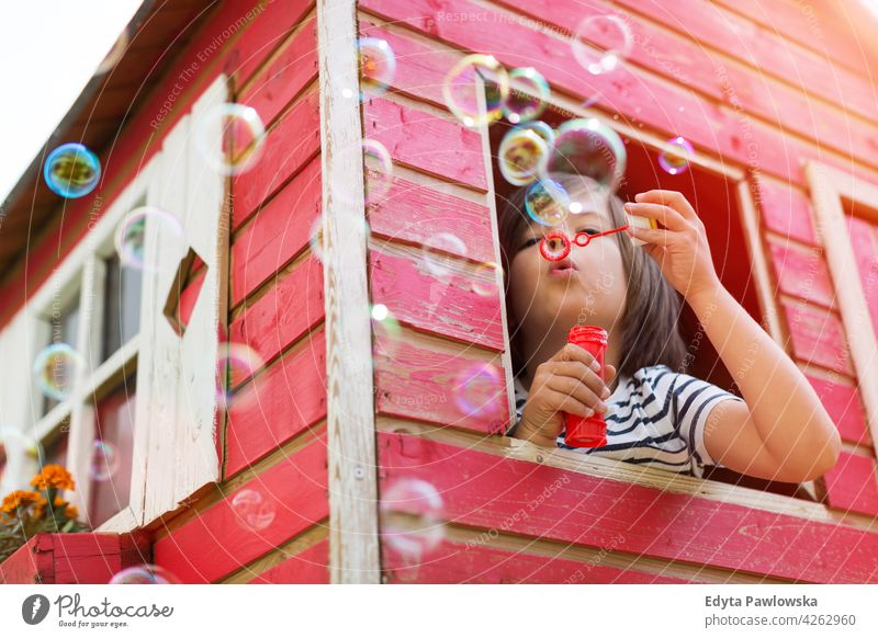 Boy blowing bubbles in a wooden playhouse red Sweden tree tree house treehouse summer outdoors adventure playful real people simple living playing sunny