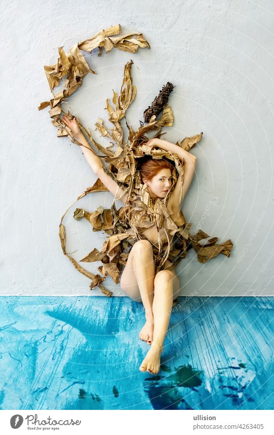 Young sexy woman with red hair artfully covered with dry, withered decorative banana tree leaves sitting on the blue floor. copy space studio floor. copy space