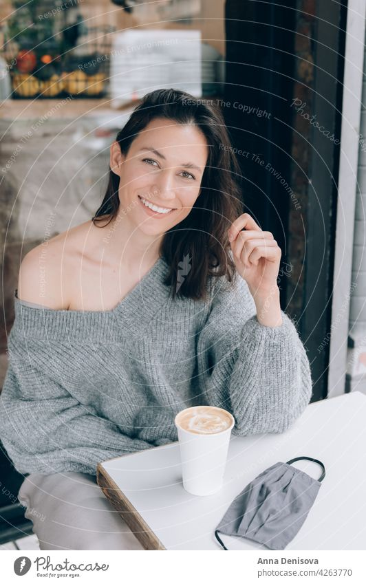 Young lady is drinking coffee at the cafe cup woman portrait young face mask smile lockdown lifted beautiful female casual brunette table happy person adult