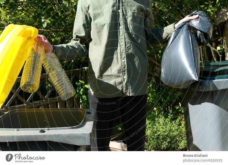 One person performing a selective sorting of household waste in recycling bins. Man putting plastic bottles in a yellow container and garbage in a bag in a green container.