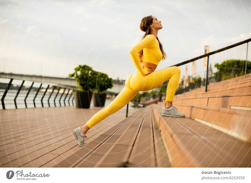 Young woman stretching on the riverside young jogging training fitness up female runner athlete people lifestyle healthy person body summer legs sportswear