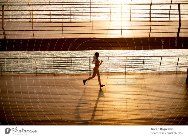 Young woman taking running exercise by the river promenade young jogging yellow training athlete people lifestyle healthy person adult sport activity city