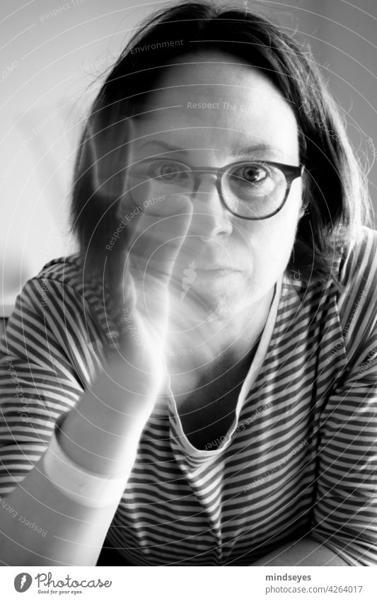 Woman with glasses waves portrait Black & white photo Striped sweater Eyeglasses motion blur Wave waving hand Looking into the camera Forward Earnest Calm