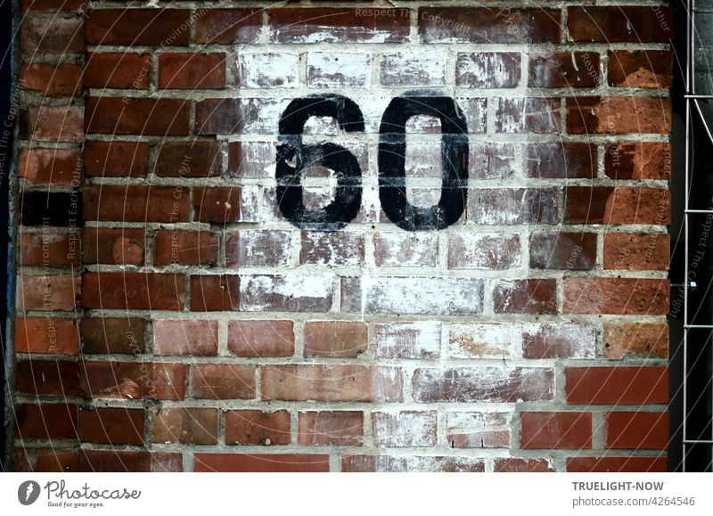 The number 60 (sixty) was painted in large black numerals on a carelessly whitewashed square on the reddish brown brick wall of an old building, perhaps representing a house number