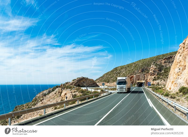 Truck with refrigerated semi-trailer driving along a road by the sea. Refrigerated Beach truck transport Exterior shot Landscape Coast Mediterranean perishable