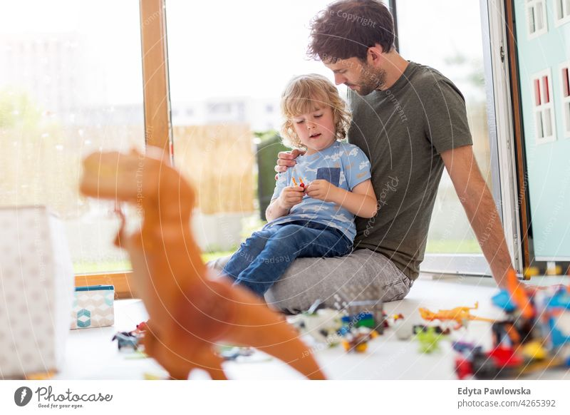 Father playing with his little son at home toys block floor children's room man dad father family parents relatives boy kids relationship together togetherness