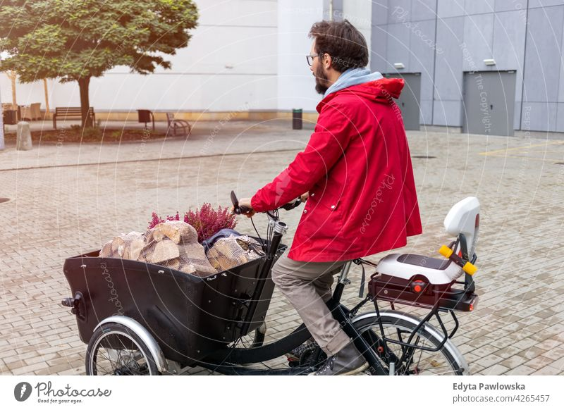 Man going back from shopping with a cargo bike carrying tricycle day healthy lifestyle active outdoors joy bicycle biking activity cyclist enjoying bike ride