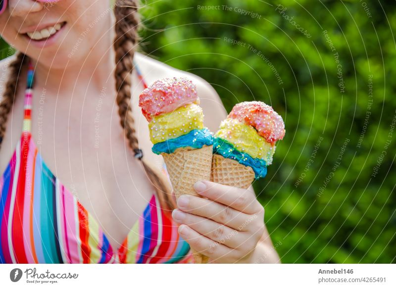 Beautiful girl holding two colorful ice cream with sprinkles wearing a rainbow colored swimsuit in the summer, pink sunglasses and braids happy vacation,holidays concept