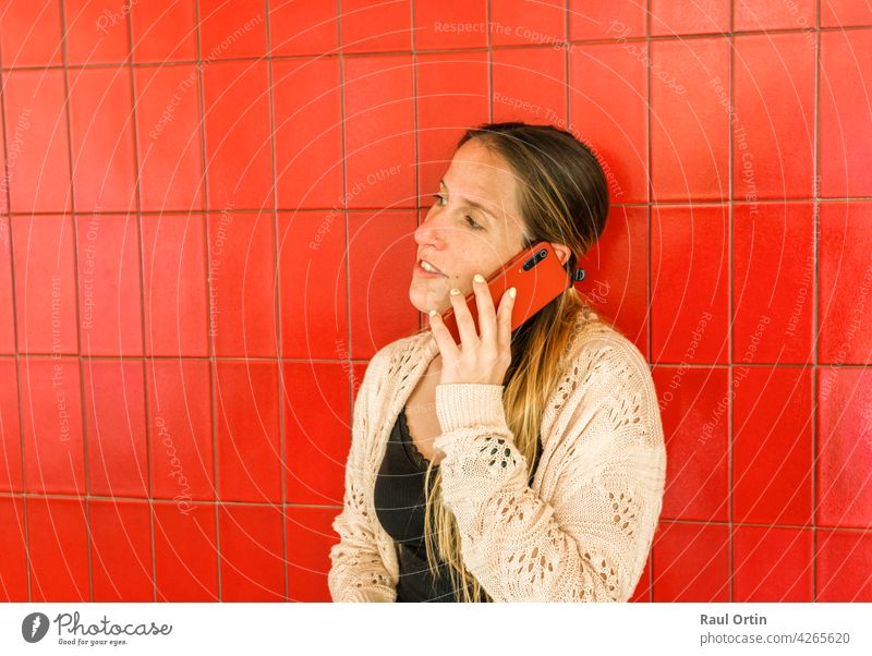Woman talking on cell phone on red background.Female using phone, making a call, technology lifestyle. person woman smartphone cellphone concept outdoor use