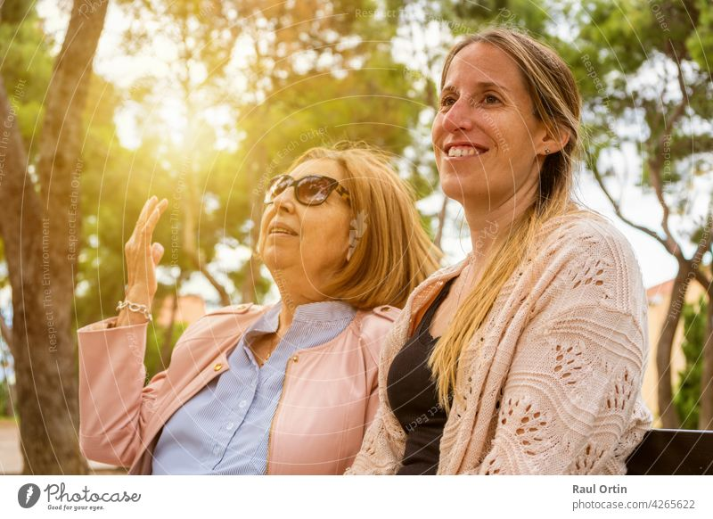 Happy family having fun on weekend.Elderly mother and her adult daughter talking and enjoy time together in nature park at sunset. women happy young woman old