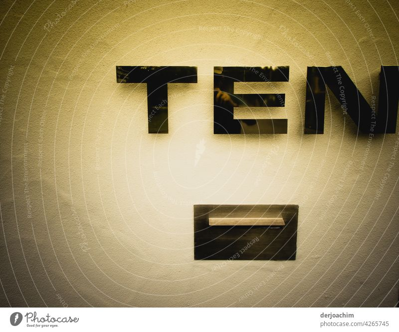 House number T E N , with mailbox underneath.  The house wall in the tender yellow. The letters and the insertion is held in black. Characters