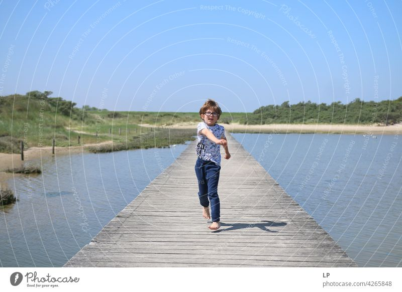 boy running on a wooden dock lonely Think Infancy Concern solitude pensive people abuse Expression Pain Fatigue Abstract Human being Exterior shot Education