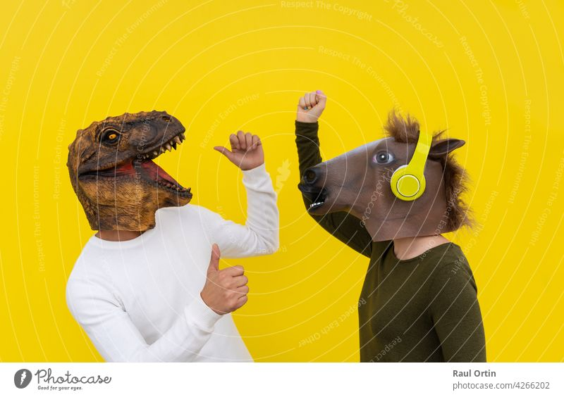 Funny couple of happy young man and woman with dinosaur and horse head mask dancing. Positive and euphoric people lifestyle, isolated on yellow background in studio with blank wall for copy space .