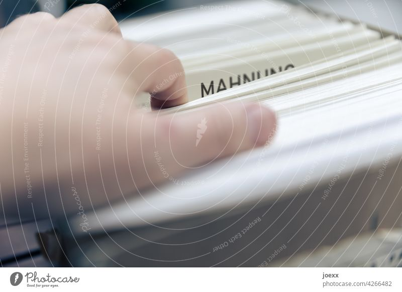 Hand on reminder in a big pile of paper dunning Paper Office Office work Debts Late payment Paying Arrangement Piece of paper Default Interior shot Colour photo