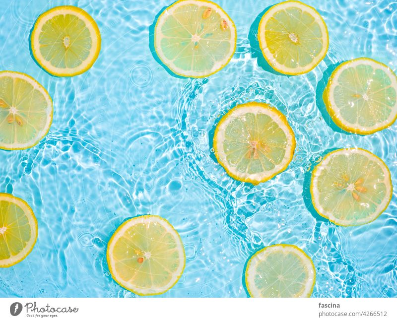 Lemon slices in clean transparent water, blue bg lemon citrus yellow splashing flat lay background copyscape flatlay splashes waves bubbles underwater surface