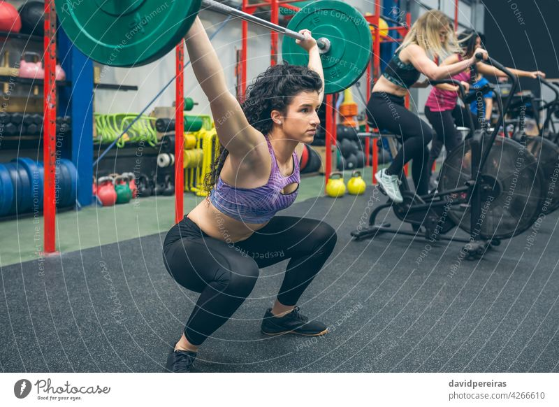 Woman practicing weightlifting in the gym woman dumbbell snatch arms up determination overcoming over head squat sportswoman self confident train strength