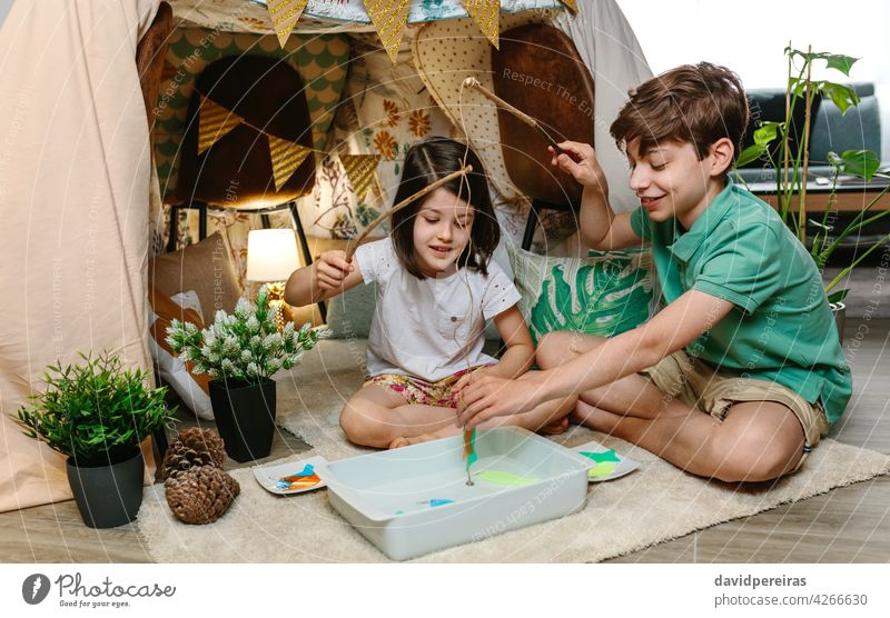 Children camping at home playing fishing game happy children diy fishing game homemade tent fishing pole home vacation staycation enjoying lockdown sister