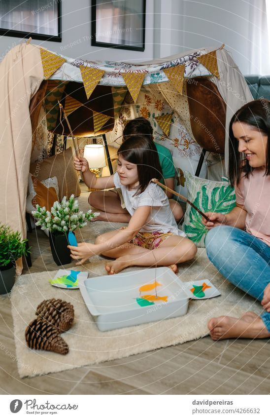 Happy mother and daughter camping at home playing diy fishing game home vacation happy family fun at home smiling diy tent fishing pole child people indoor