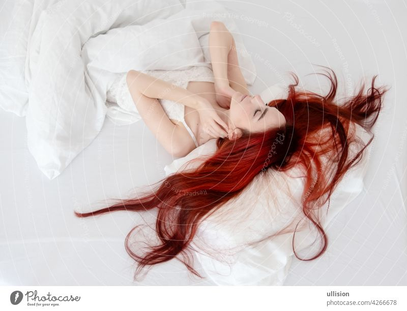 Top view of attractive, contented, young, sexy, woman with dyed bright red hair relaxing in bed, enjoying soft sheets and mattress in bedroom, copy space. Woman