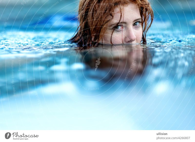 Portrait of young sexy woman with red hair, redhead swimming in the pool, head half submerged under water, copy space wet summertime enjoyment attractive