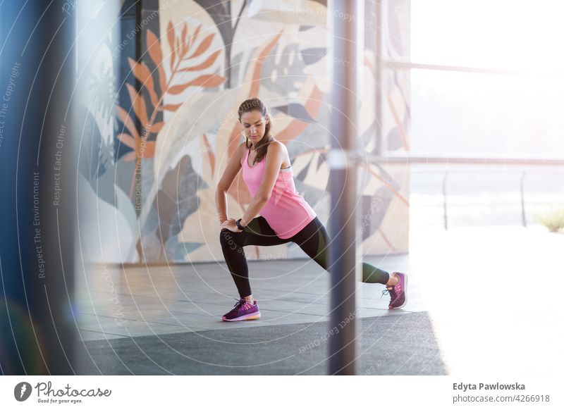 Young woman doing fitness exercise in urban area energy exercising sport activity vitality body gym clothes training workout effort flexible flexibility city