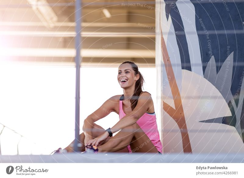 Sporty young woman in a urban city area energy exercising fitness sport activity vitality body gym clothes training workout effort flexible flexibility active