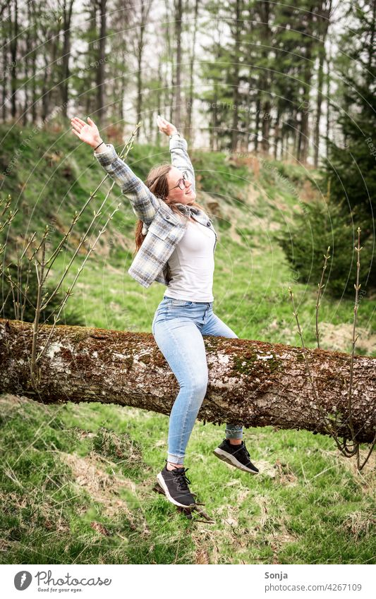 Young woman with raised arms sitting on a tree trunk in the forest Tree trunk Sit Joy Laughter Happy Happiness Exterior shot Forest Joie de vivre (Vitality)