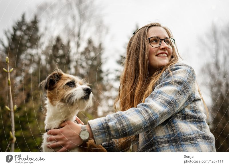 Young smiling woman with glasses and a small dog outside in the park Woman Smiling youthful Dog Terrier Small Park Tree Pet Cute Happy Lifestyle pretty portrait