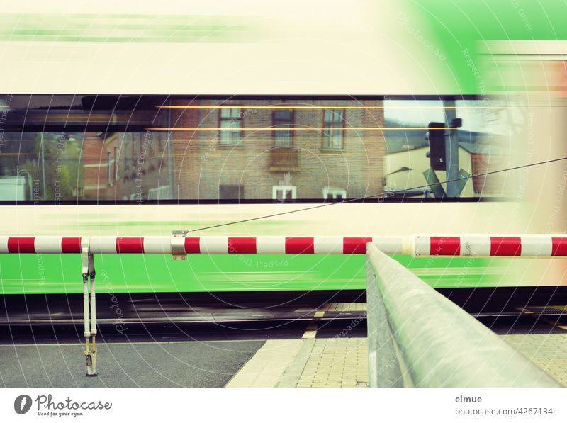 A train passes a closed level crossing, houses are reflected in its windows / motion blur / travelling / rail traffic Train Railroad crossing Train travel Track