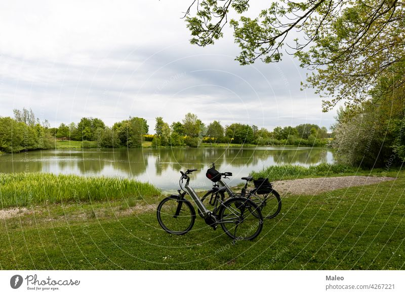 Bicycles stand on the shore of a small lake activity adult autumn beach beautiful bicycle bike blue boat city coast cyclist europe harbor harbour landscape