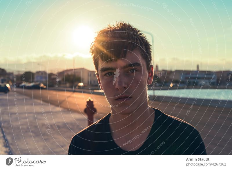 portrait of a serious teenager with the sun behind his head young man sad worried tired sunset harbor pier backlit sunlight evening street outdoors beautiful