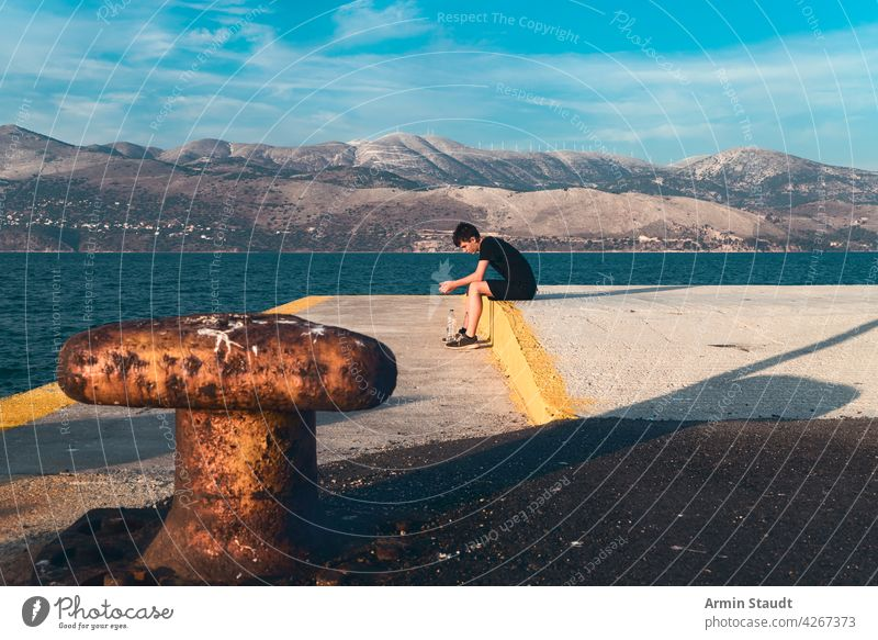 pensive teenager sitting on a pier by the sea with beautiful scenery in the background young man sad serious alone lonely bottle water harbor worried landscape