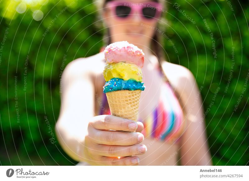 young female in rainbow colored swimwear giving ice cream, two colorful different flavors ice cream scone in hand with sprinkles in the summer, food,spring,Holiday,vacation concept