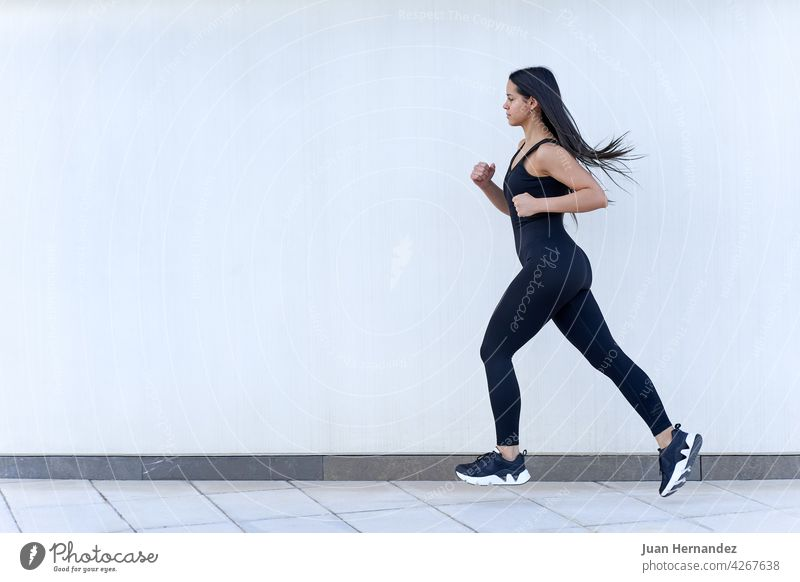 Young woman with fit body running in sportswear young jumping female model exercising athlete exercise fitness training runner horizontal athletic speed