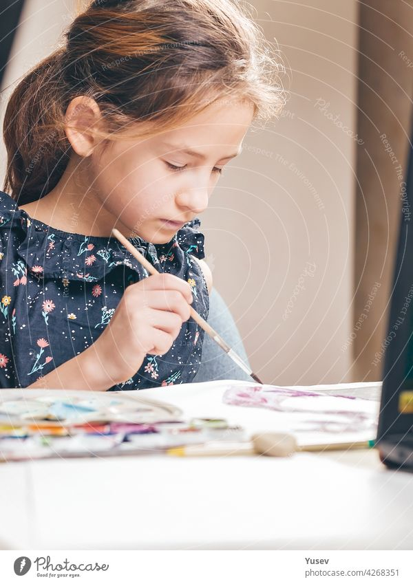 Cute lovely girl draws with paints. Ideas for activities with children at home. Vertical shot cute school sitting table drawing color studies ideas learning