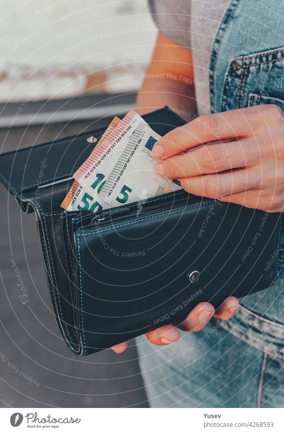 Female hands hold a wallet with euro banknotes. The concept of finance, savings, financial expenses. Close-up. Vertical shot female holding currency economic
