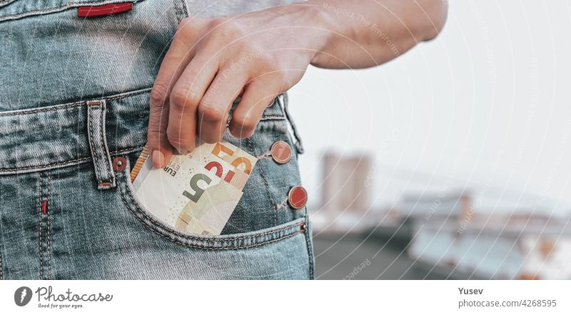 WEB banner format. A womans hand takes out euro from her jeans pocket. The concept of finance, savings, financial expenses. Close-up. Copy space web taking