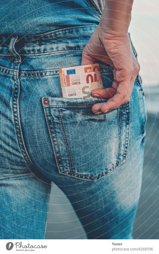 A woman's hand takes out euro bills from the back pocket of her jeans. The concept of finance, savings, financial expenses. Close-up taking banknote blue money