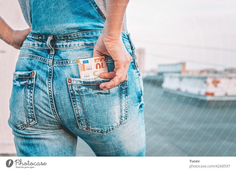 A womans hand takes out euro bills from the back pocket of her jeans. The concept of finance, savings, financial expenses. Close-up. Copy space taking banknote