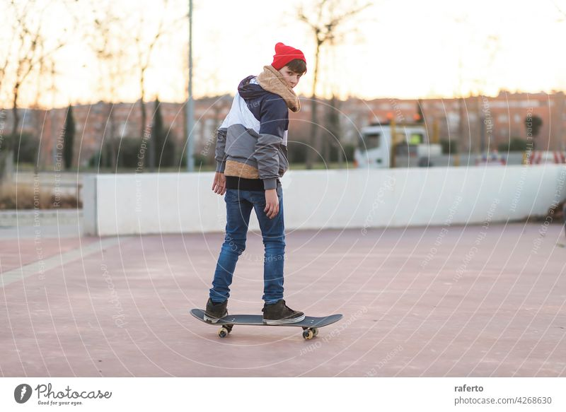 Teenager skateboarder boy with a skateboard on asphalt playground doing tricks. children teenage person sport action cool dynamic guy hipster practice