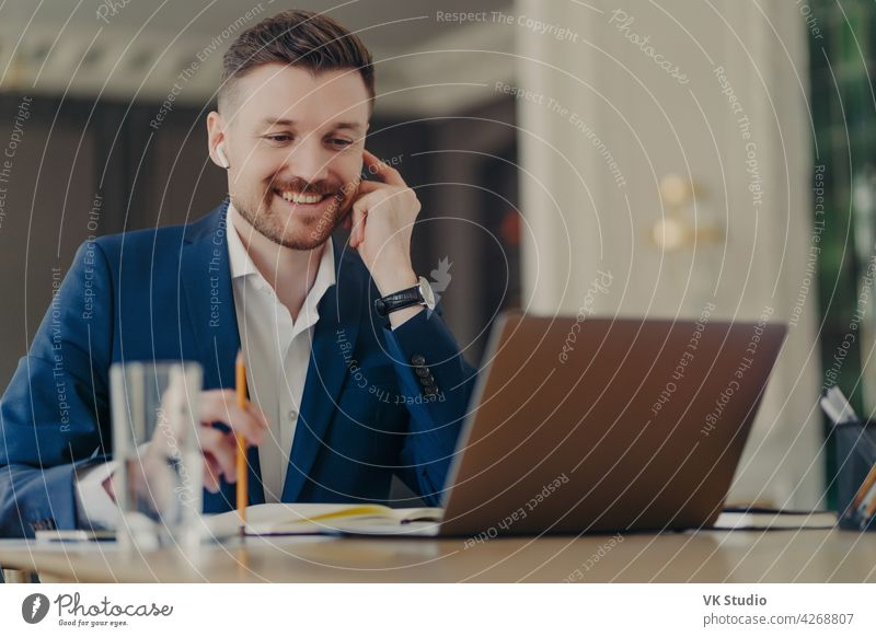 Successful happy CEO having online meeting, using laptop and earphones businessman smiling video conference web conference talking office handsome thinking