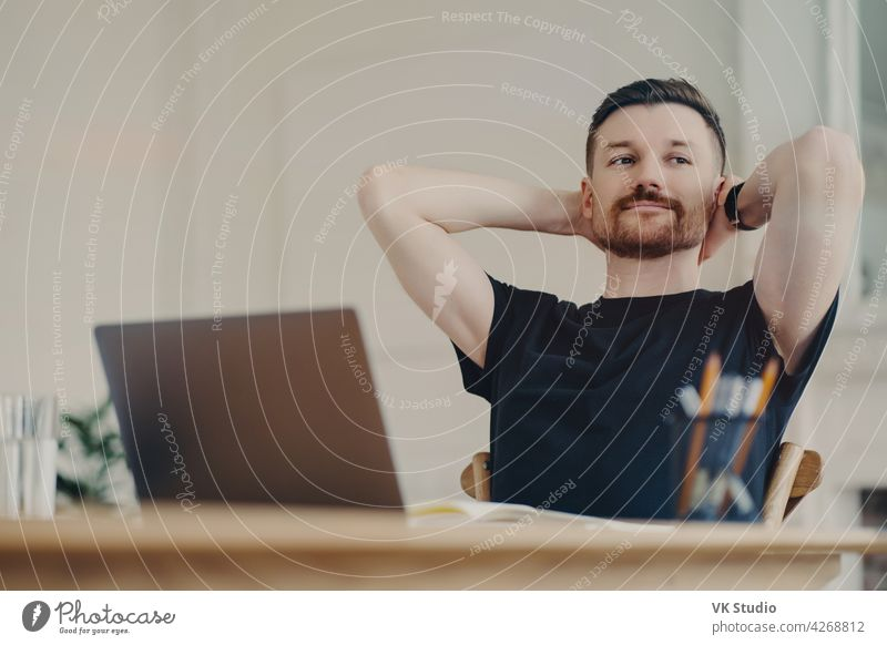 Happy business person resting after work while sitting at his workplace at home freelancer businessman office worker relaxed laptop happy work done computer